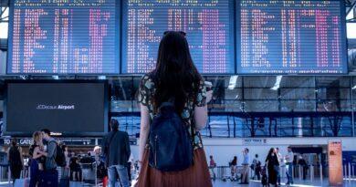 Jeune fiille touriste devant le panneau d'affichage d'un aéroport